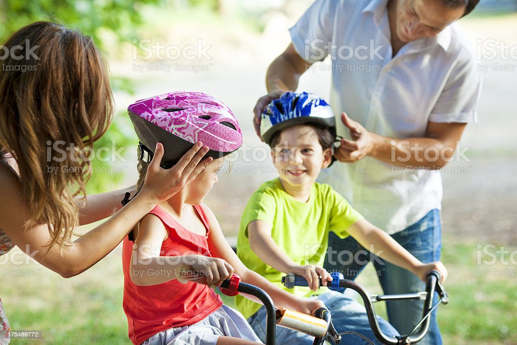 Parents Helping Children With Cycling Helmets. stock photo
