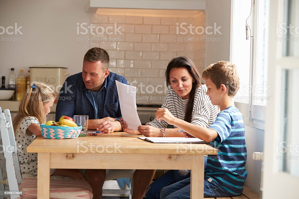 Parents Helping Children With Homework At Kitchen Table stock photo
