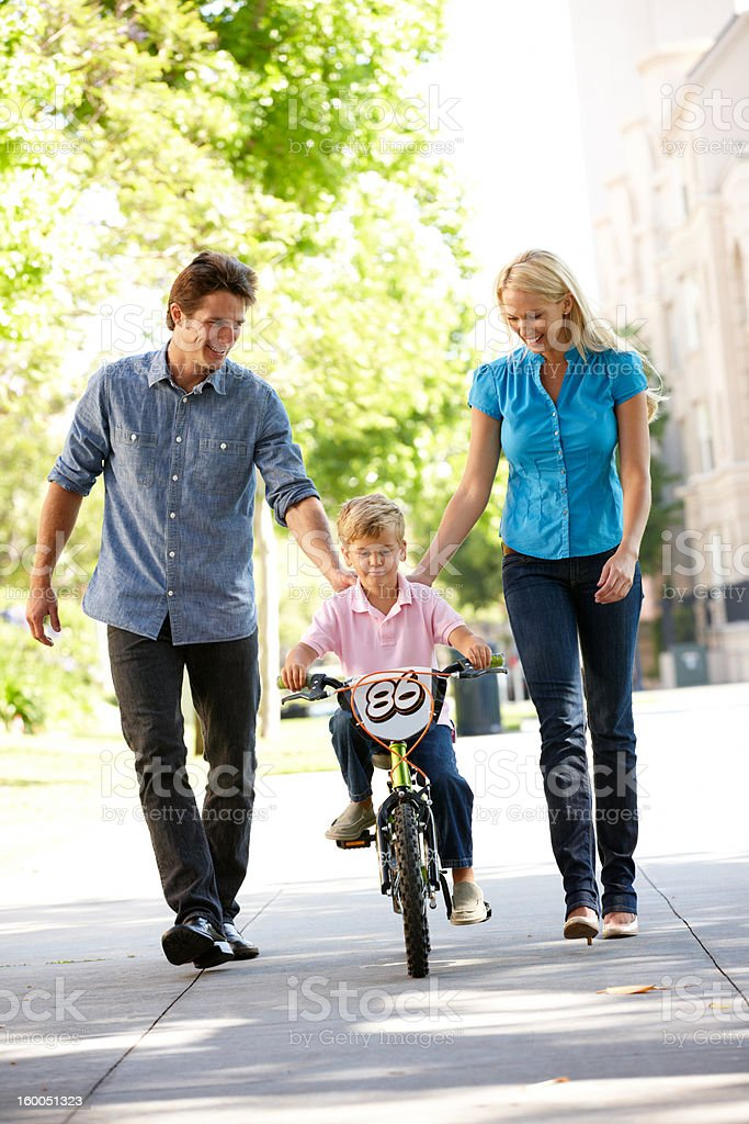 Parents helping son to ride bike royalty-free stock photo