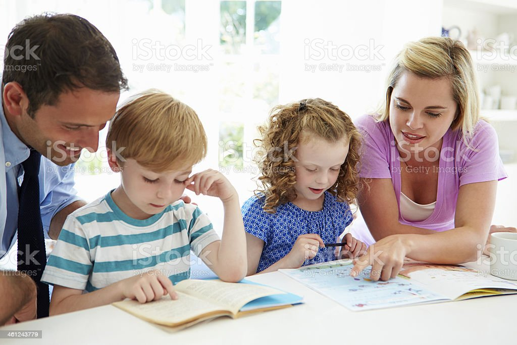 Parents helping their children with their homework stock photo