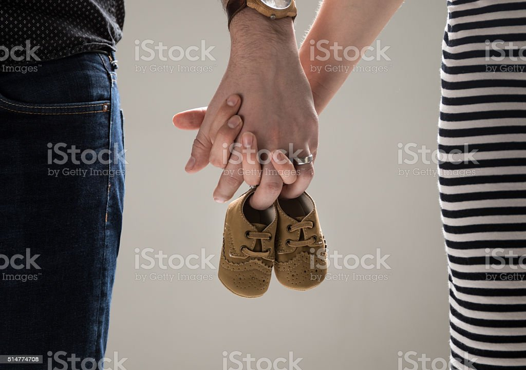 Parents holding baby shoes stock photo