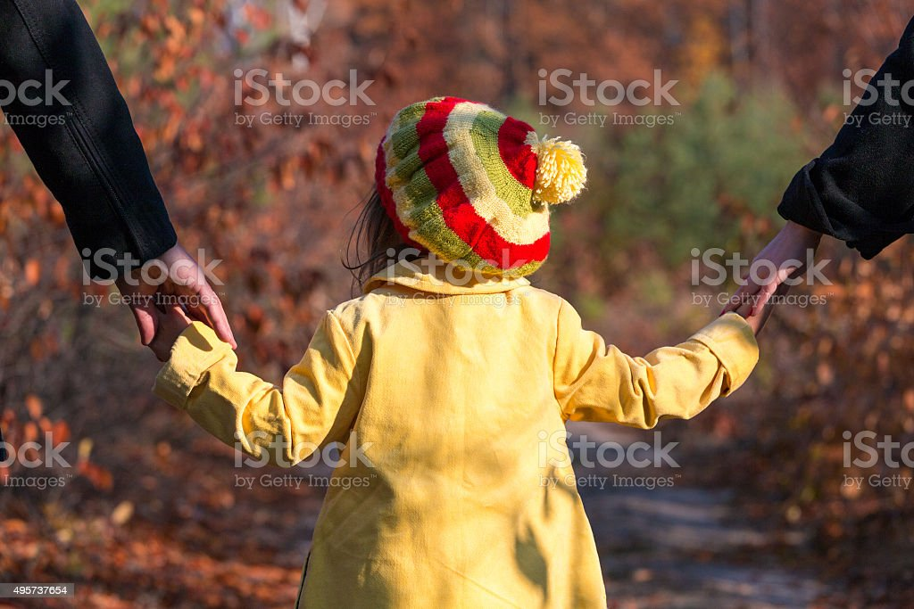 Parents Holding Hands of Little Baby Daughter in Park stock photo