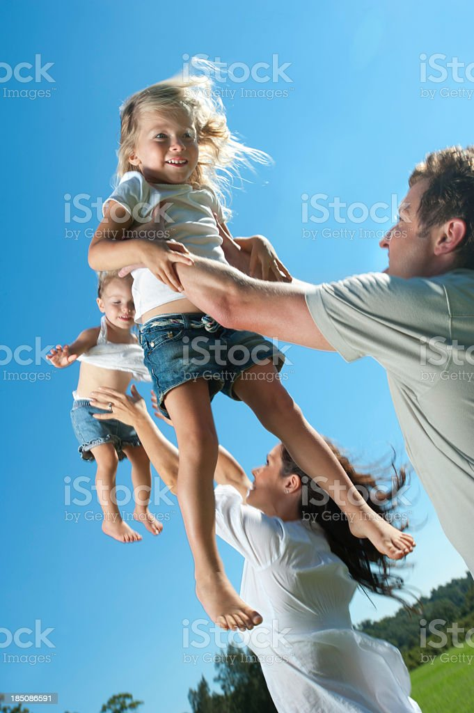 Parents joyfully throwing their children in the air. royalty-free stock photo