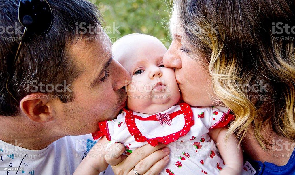 Parents kissing baby, happy family. stock photo