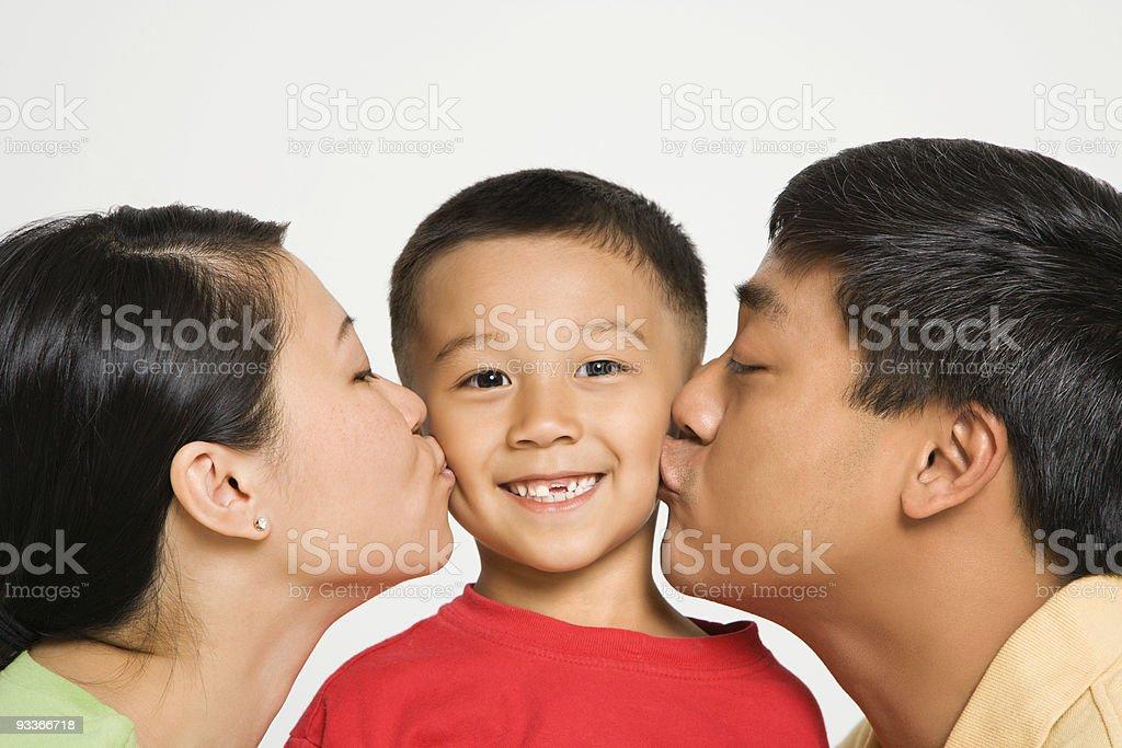 Parents kissing boy. stock photo