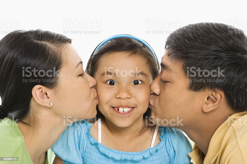 Parents kissing daughter. royalty-free stock photo
