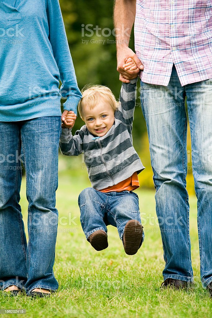 Parents lifting son by hands royalty-free stock photo