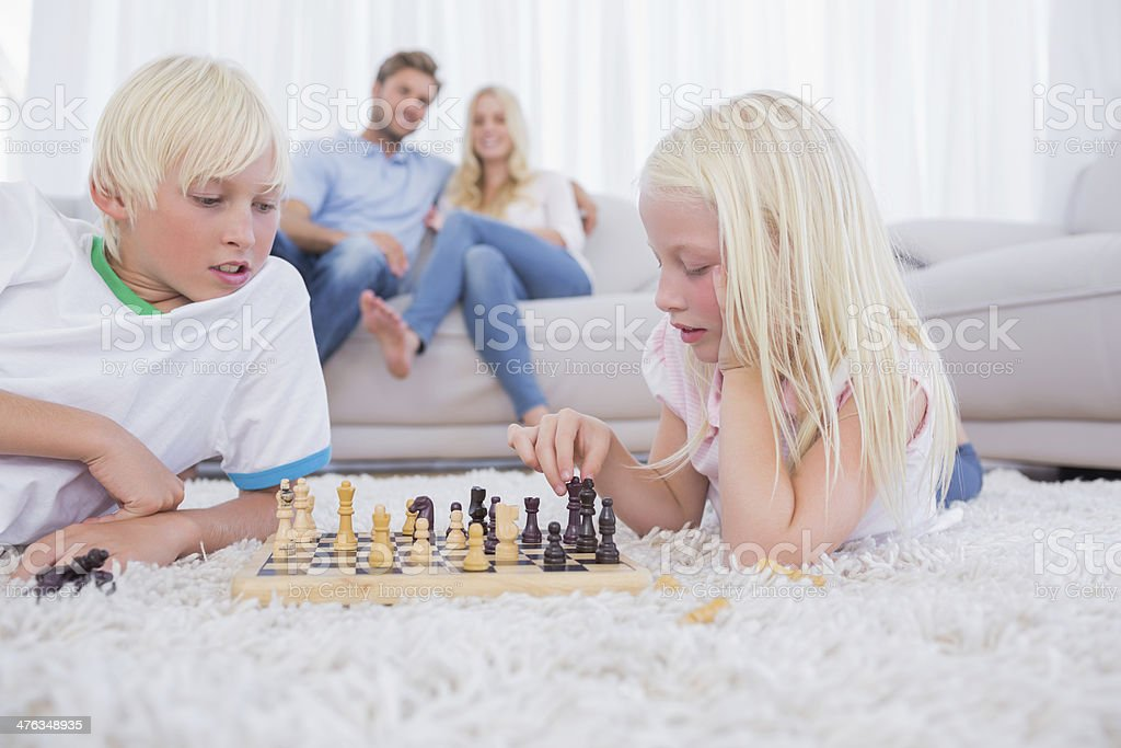 Parents looking at their children playing chess royalty-free stock photo
