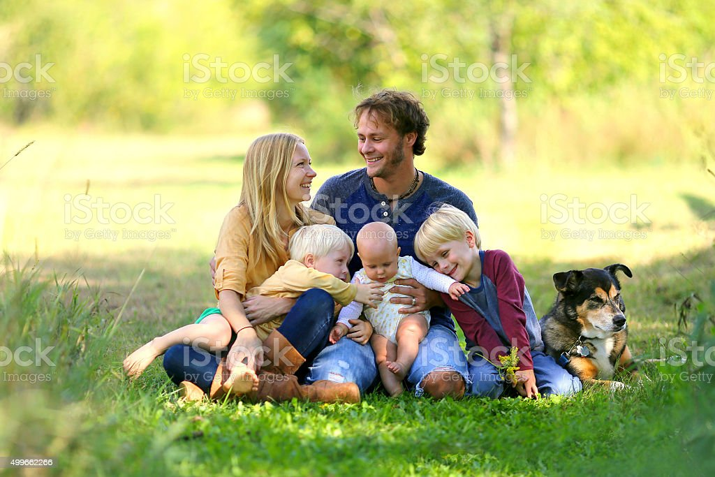 Parents Looking Lovingly at Each Other with Famil and Dog stock photo