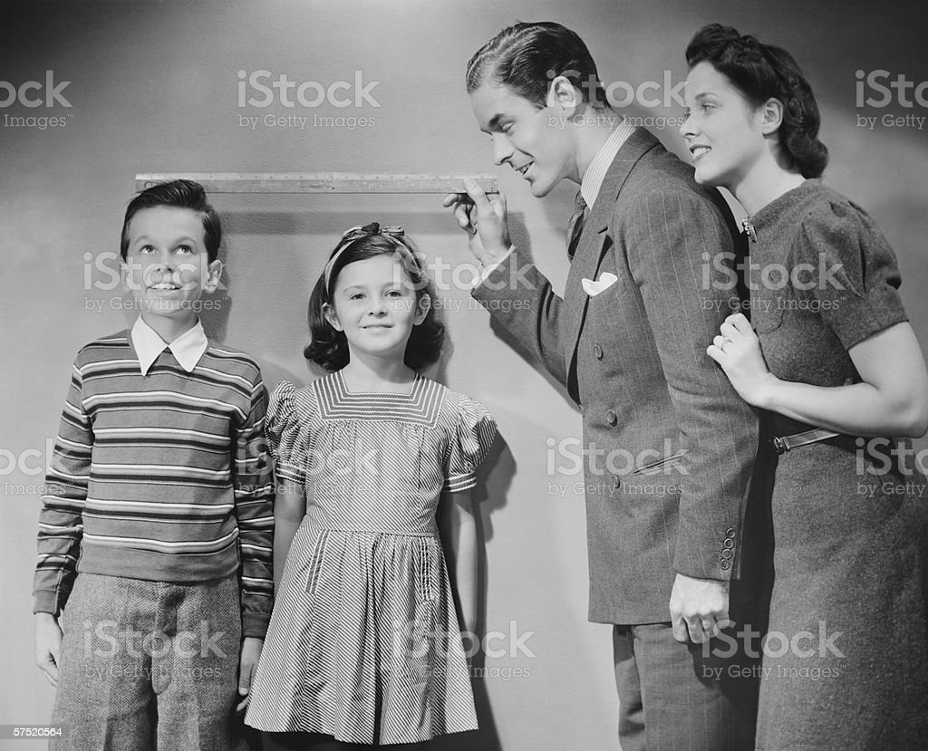 Parents measuring children standing against wall, boy (8-9) girl (6-7), (B&W) stock photo