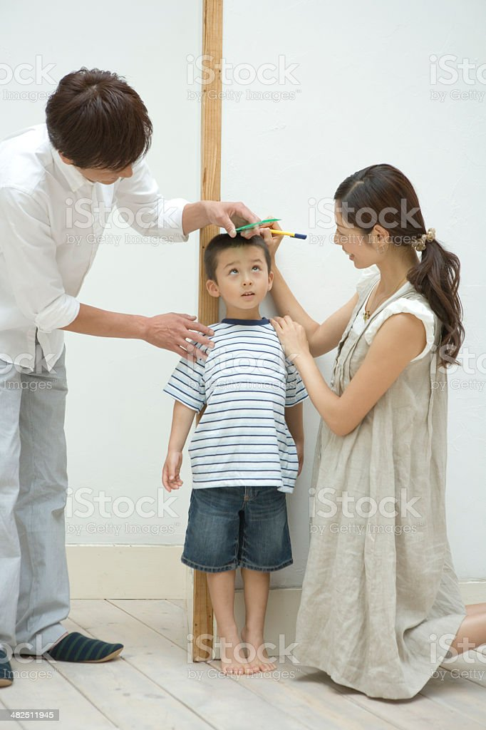 Parents measuring son's height stock photo