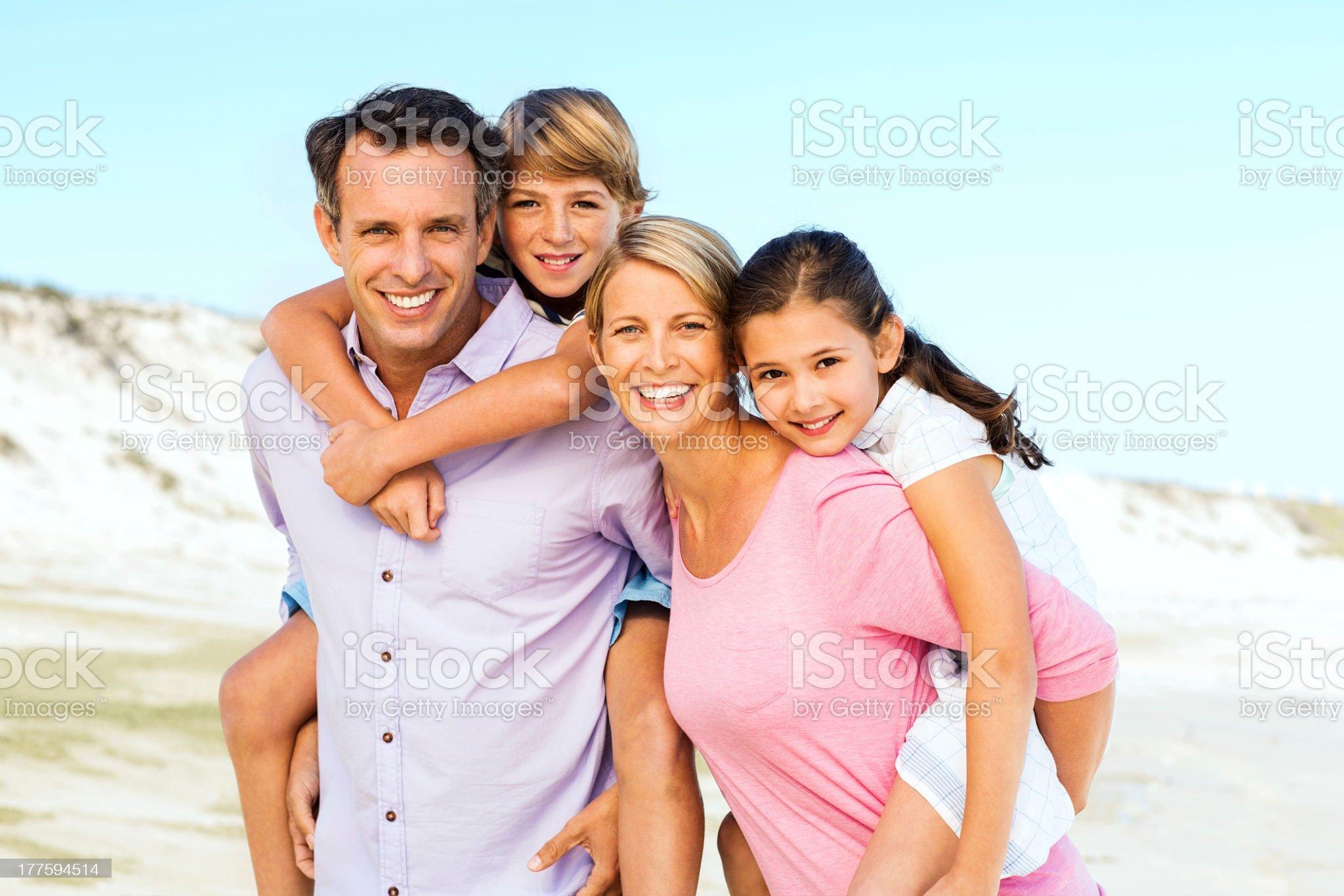Parents Piggybacking Children At Beach royalty-free stock photo