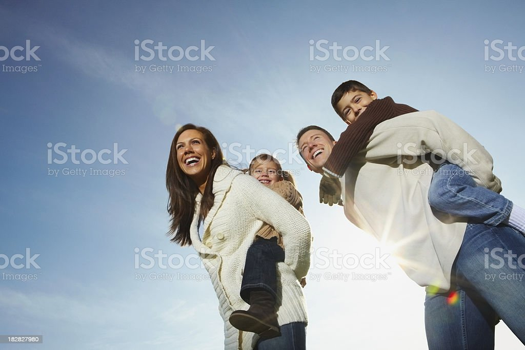 Parents piggybacking kids against sky royalty-free stock photo