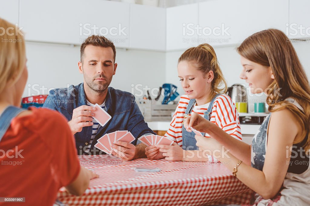 Parents playing cards with their daughters in the kitchen stock photo