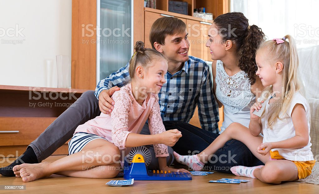 Parents playing lotto with kids stock photo