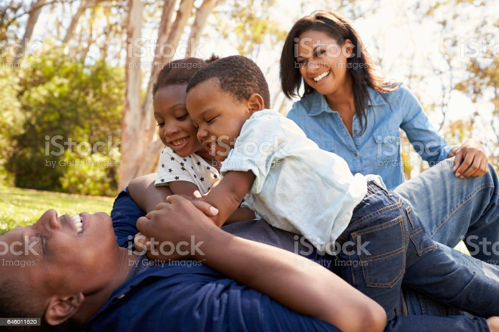 Parents Playing With Children On Grass In Summer Park stock photo
