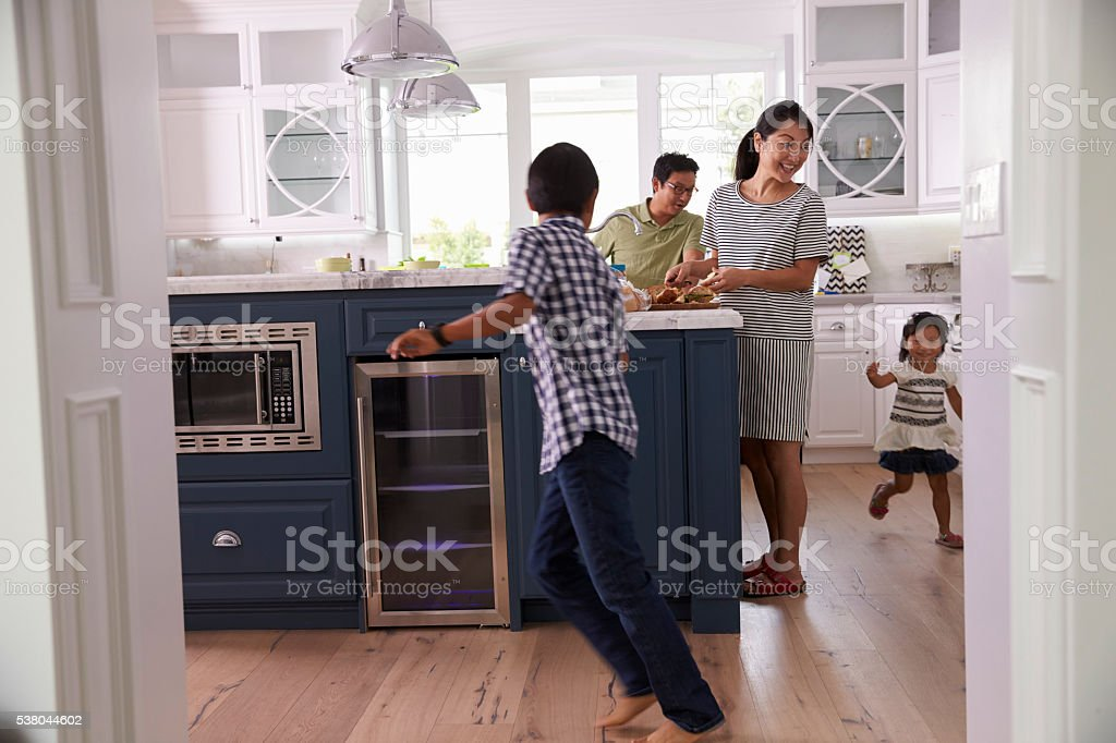 Parents Prepare Food As Children Play In Kitchen stock photo