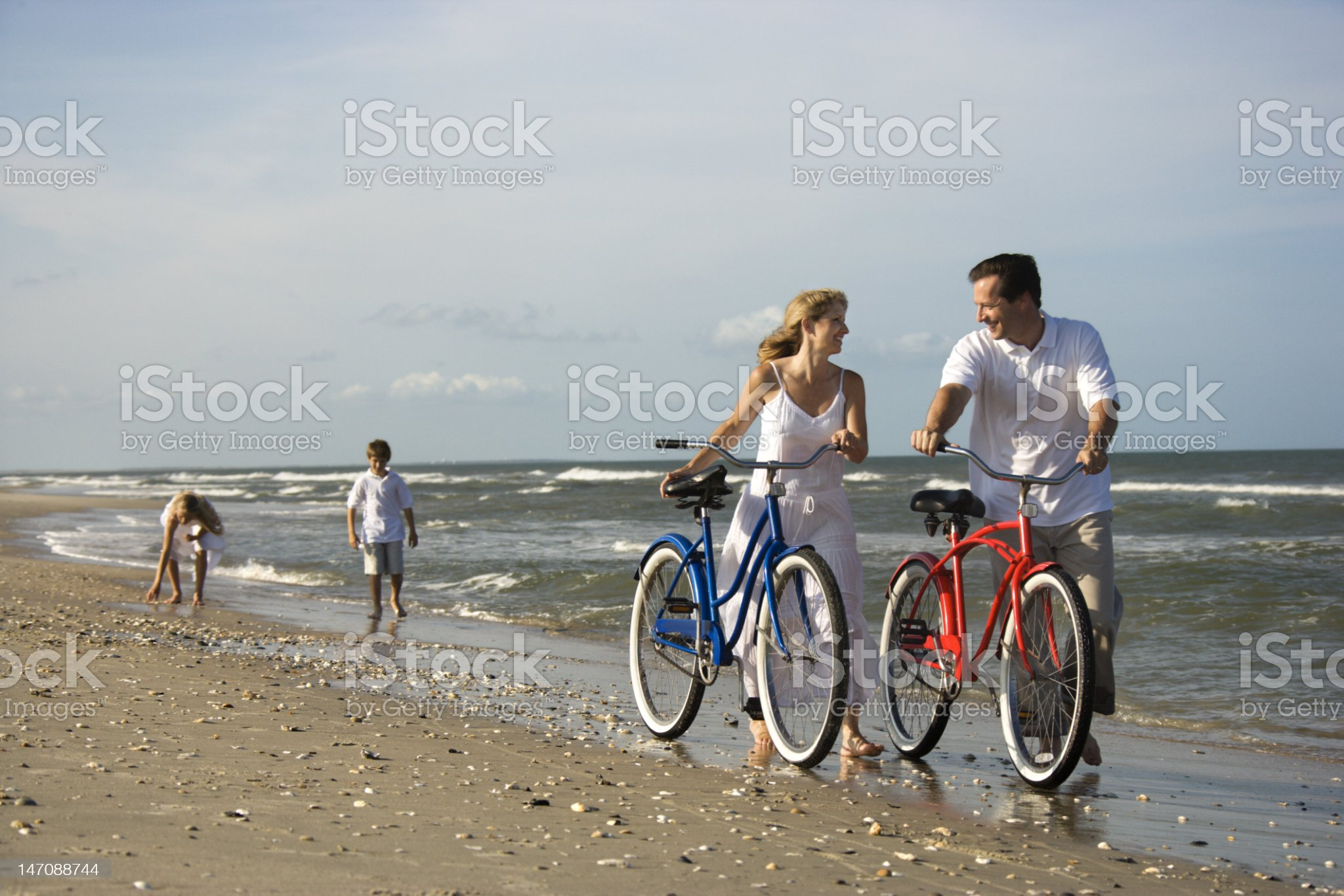 Parents pushing bikes on beach with their boys behind them royalty-free stock photo