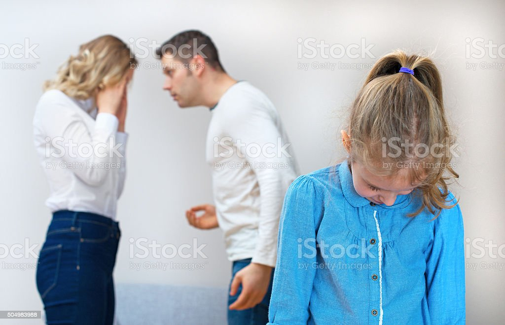 Parents quarreling at home, child is suffering. stock photo