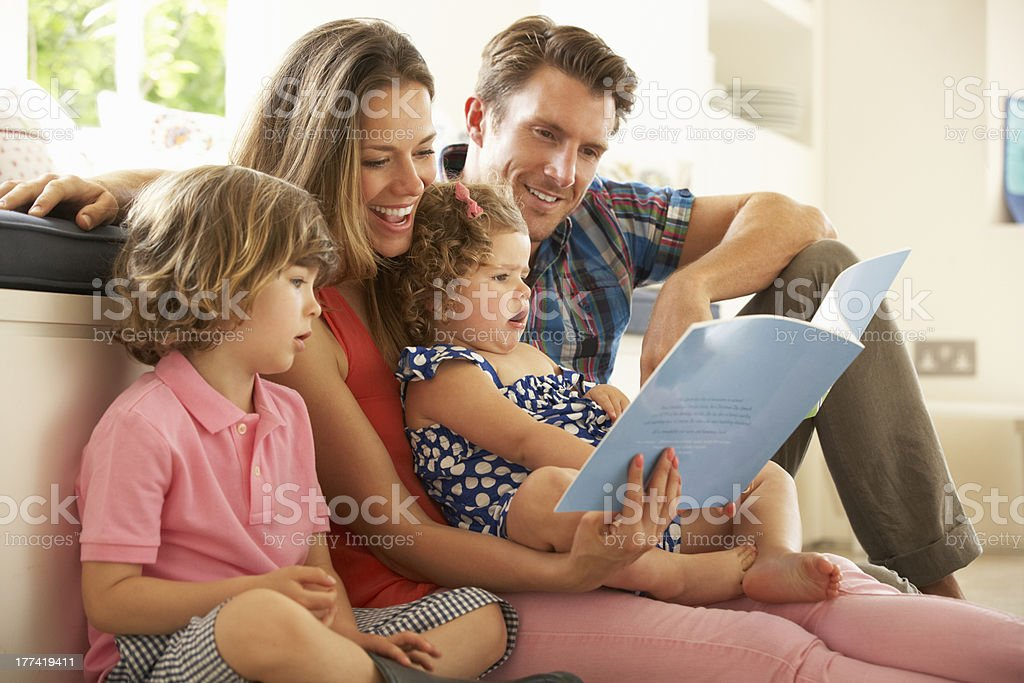 Parents Sitting With Children Reading Story Indoors stock photo