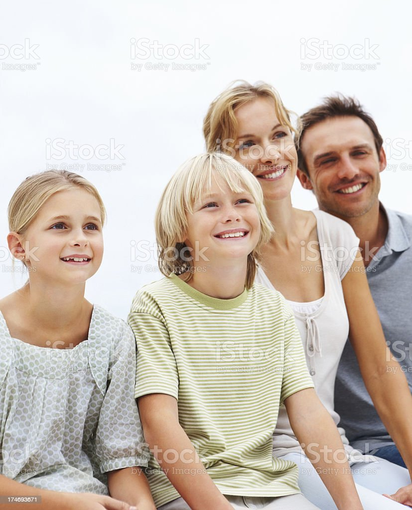 Parents sitting with their children and looking away royalty-free stock photo