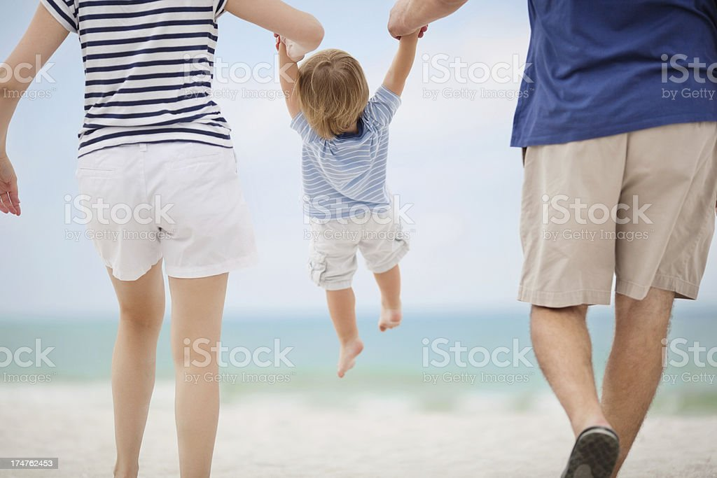 Parents Swinging Little Boy At Beach stock photo