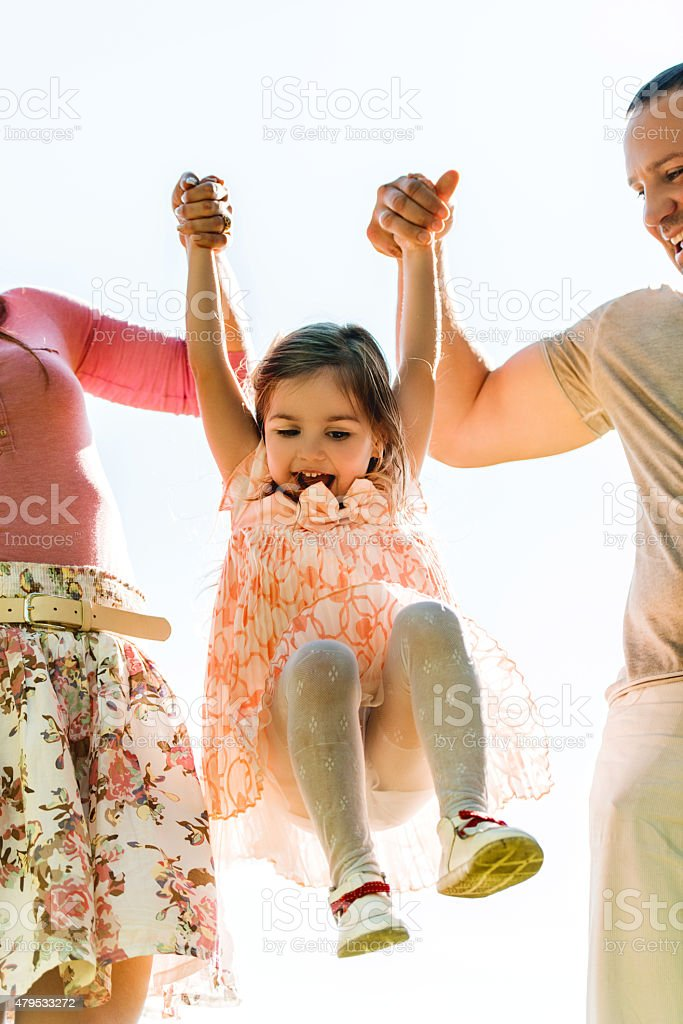 Parents swinging their little girl outdoors and having fun. stock photo