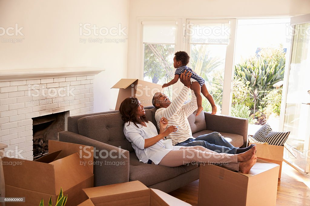 Parents Take A Break On Sofa With Son On Moving Day stock photo