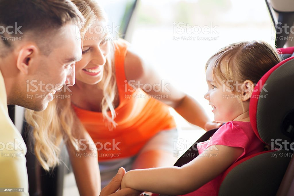 parents talking to little girl in baby car seat stock photo