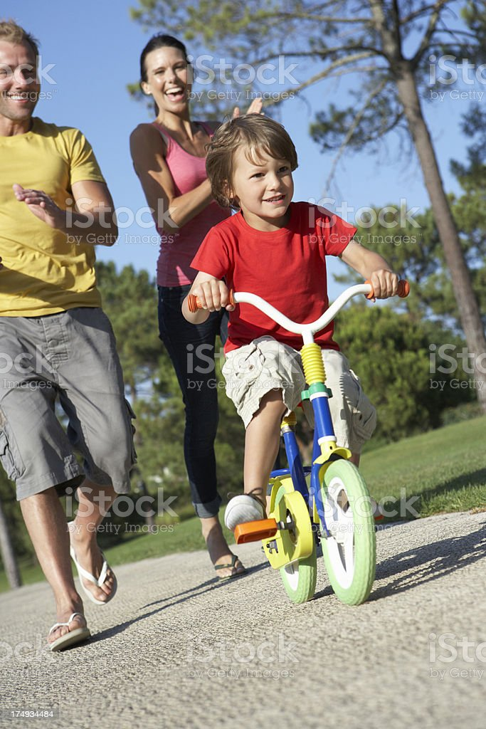 Parents Teaching Son To Ride Bike In Park royalty-free stock photo