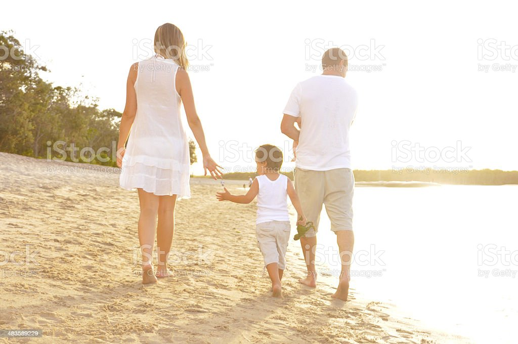 Parents walking with son on beach stock photo