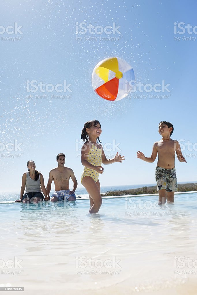 Parents watching kids play with ball in swimming pool royalty-free stock photo