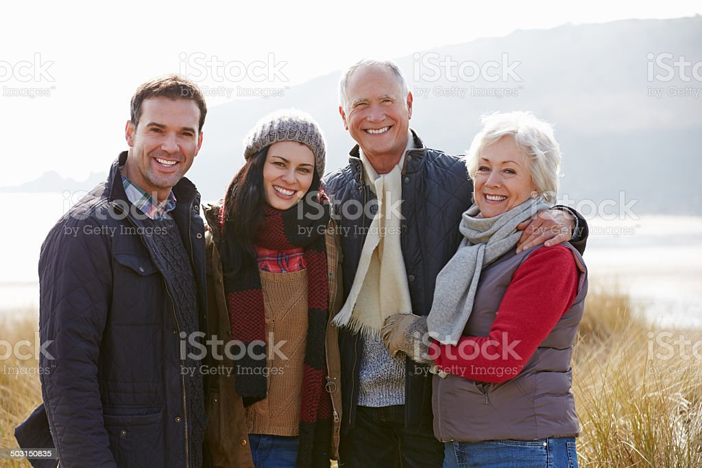 Parents With Adult Offspring Standing In Dunes stock photo