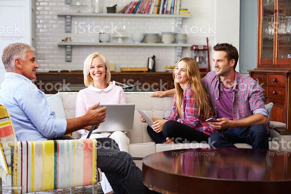 Parents With Adult Offspring Using Digital Devices At Home stock photo