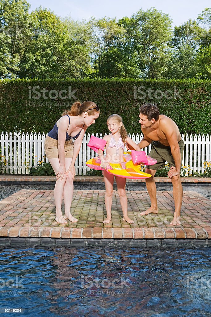 Parents with daughter by the pool royalty-free stock photo