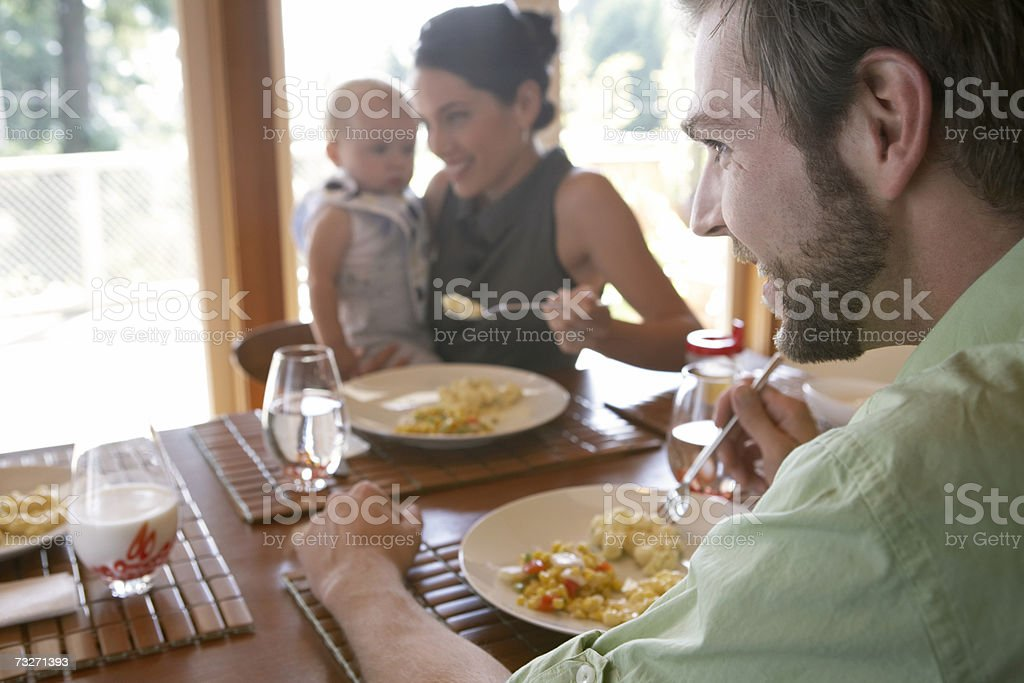 Parents with daughter (9-12 months) eating at dining table, focus on father royalty-free stock photo