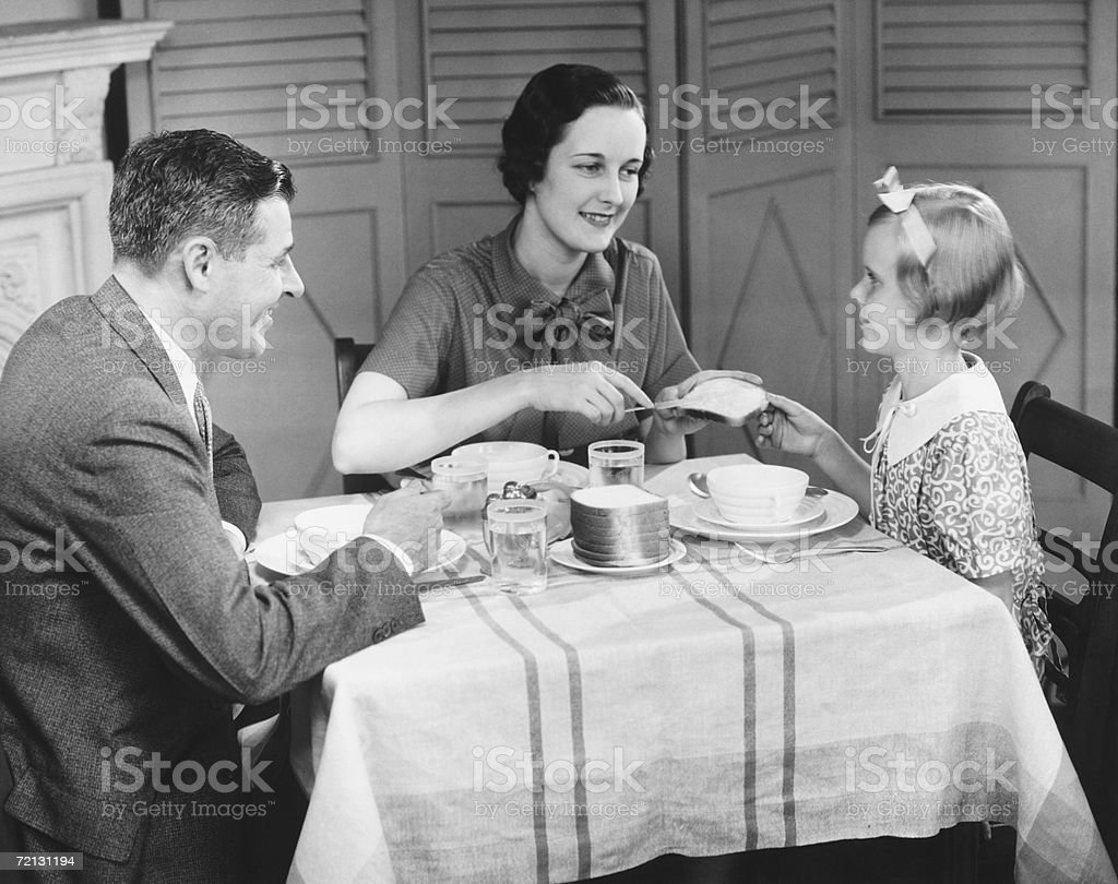 Parents with daughter (8-9) eating breakfast at home (B&W) stock photo