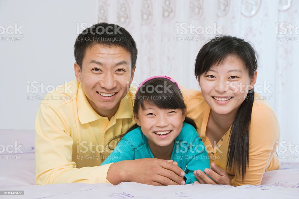Parents with daughter (8-9) lying on bed, smiling, portrait stock photo