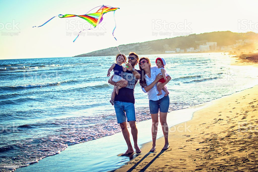Parents with daughters flying kite together at tropical sunny beach stock photo