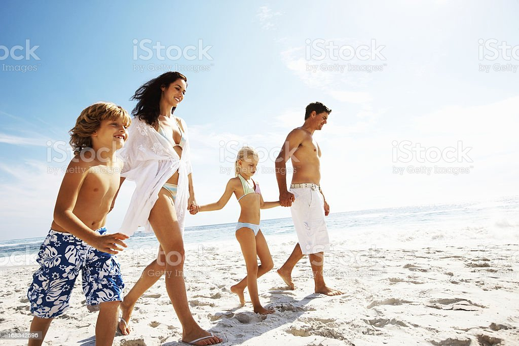 Parents with their two kids at the beach royalty-free stock photo