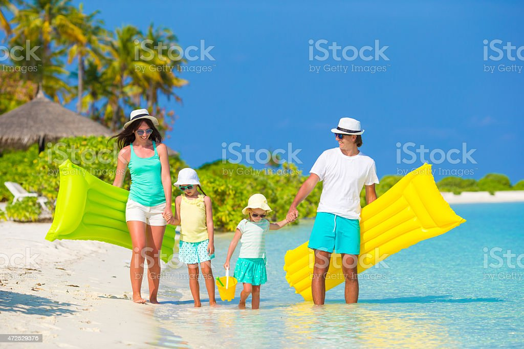 Parents with two daughters on a beach with pool mattresses stock photo