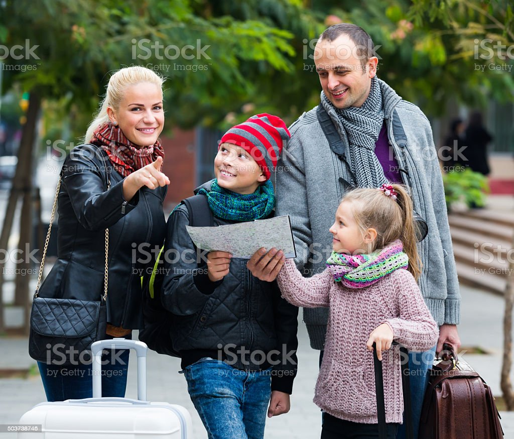 Parents with two kids and baggage with map stock photo