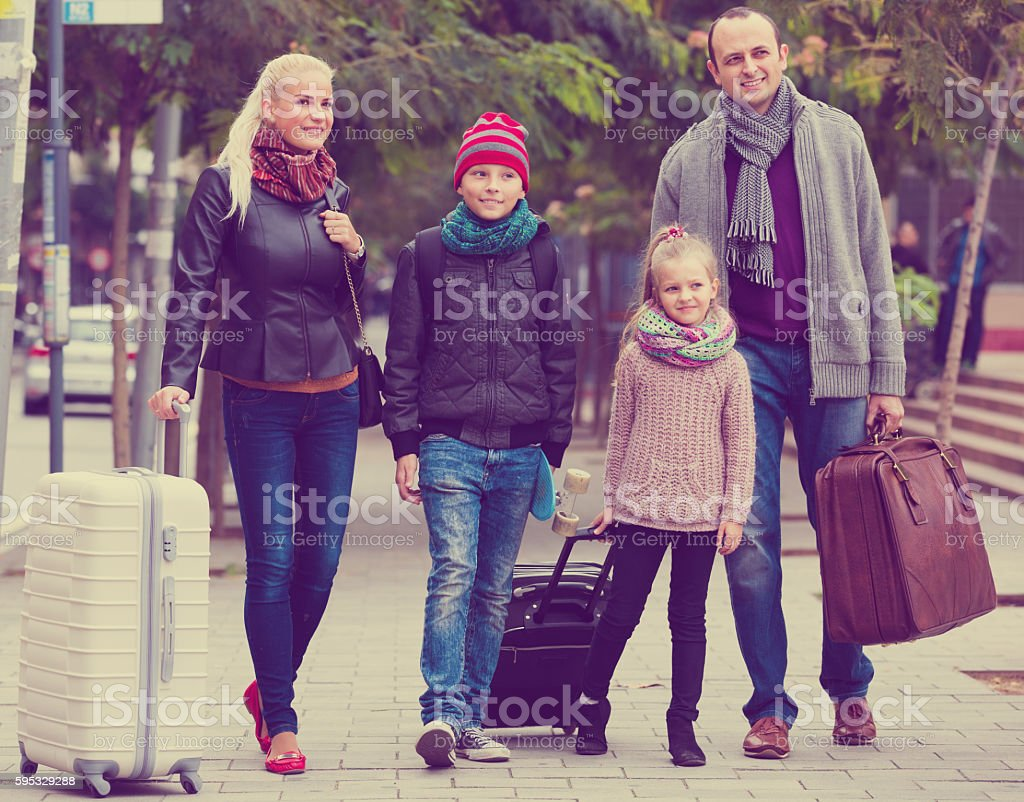 Parents with two kids chasing streets stock photo