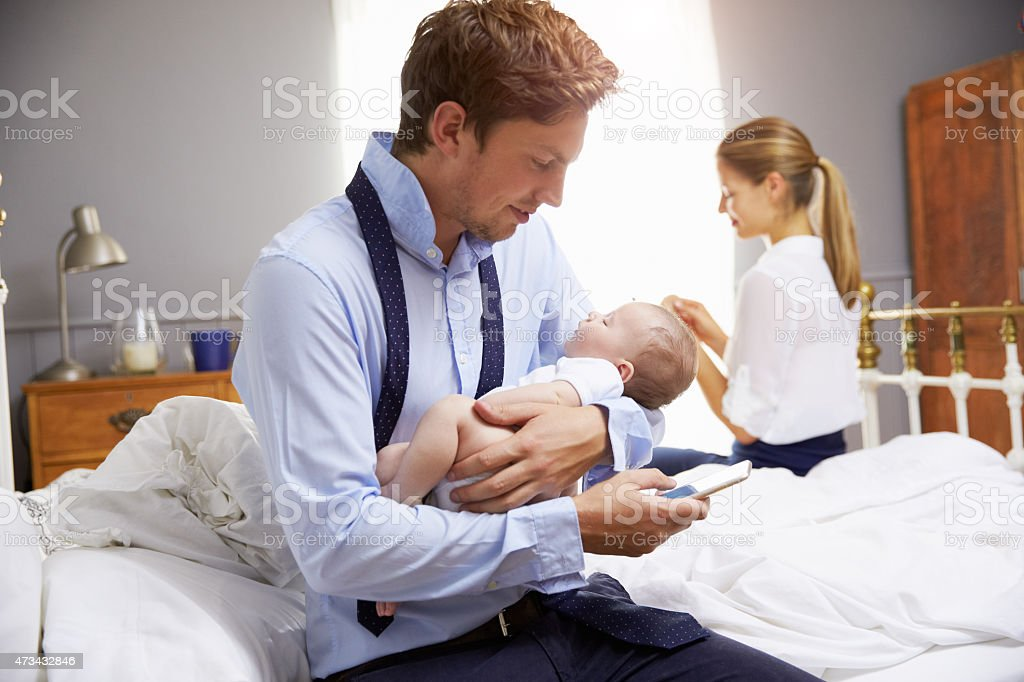 Parents With Young Baby Dressing For Work In Bedroom stock photo
