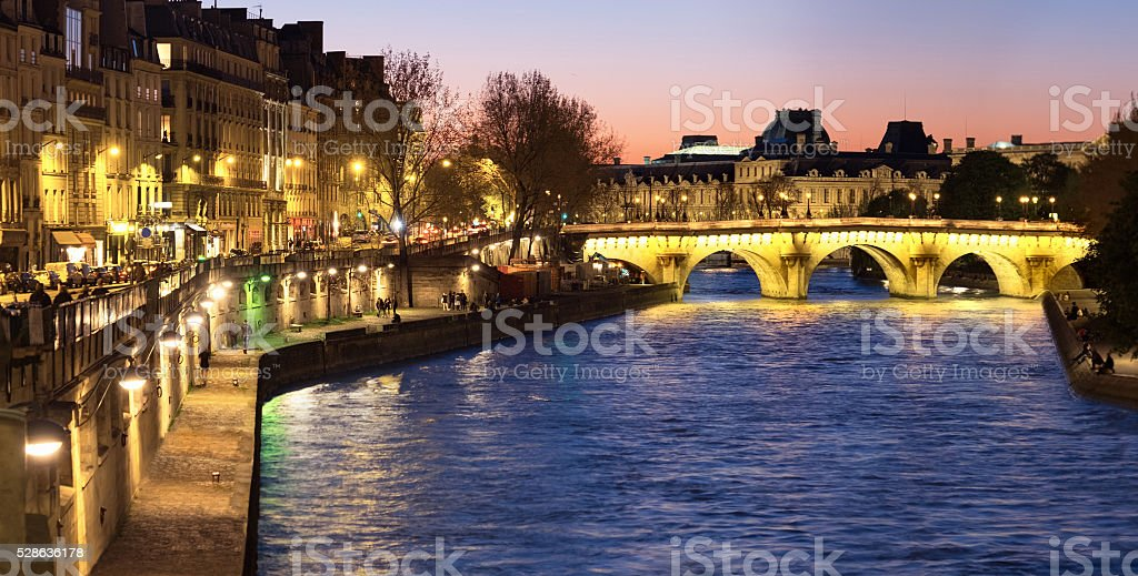 Paris, panorama along Seine river towards illuminated Pont Neuf stock photo