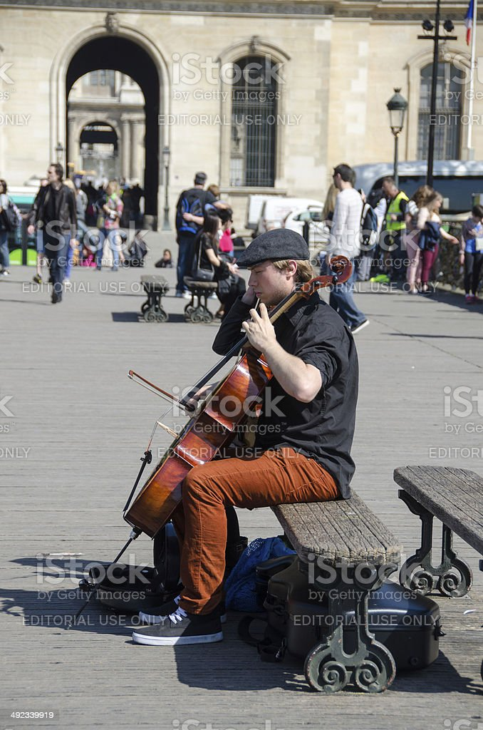 On a bridge over the Seine River a musician is playing a cello.The...