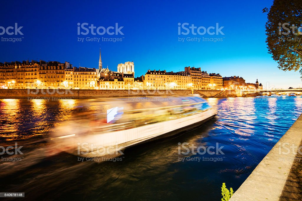 Paris with river seine and a cruising ship passing by stock photo