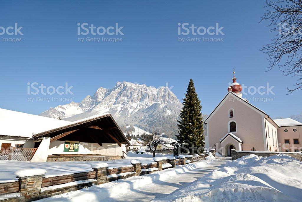 Parish church Ehrwald with Zugspitze summit, Germany's highest mountain stock photo