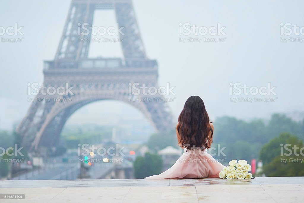 Parisian woman in front of the Eiffel tower stock photo