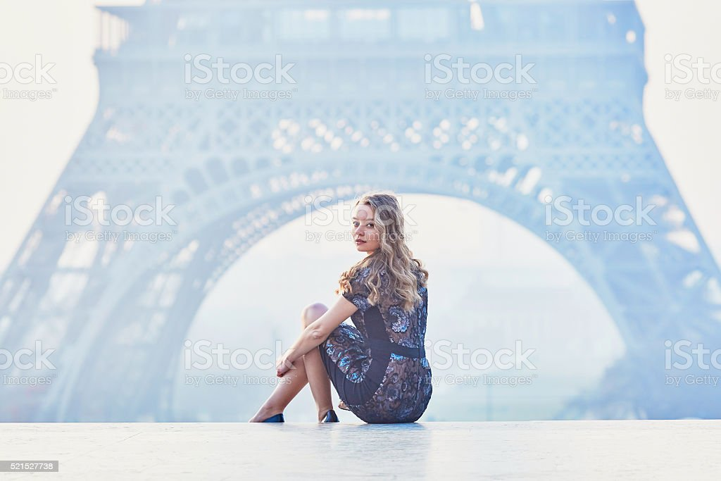 Parisian woman near the Eiffel tower at morning stock photo